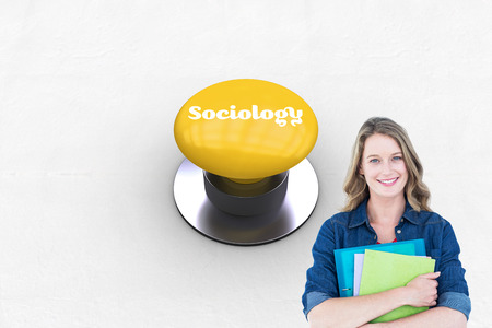 sociology: The word sociology and smiling student holding notebook and file  against yellow push button