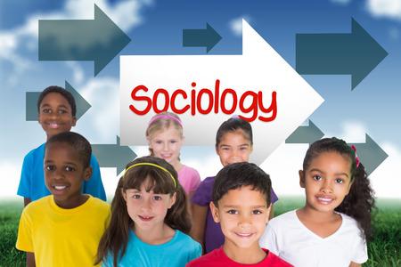 sociologia: La palabra sociología y alumnos de primaria sonriendo contra el cielo azul sobre campo verde Foto de archivo