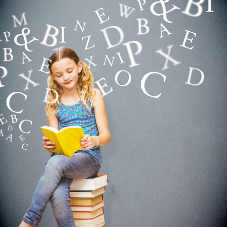 legs crossed at knee: Cute little girl reading book in library against grey background