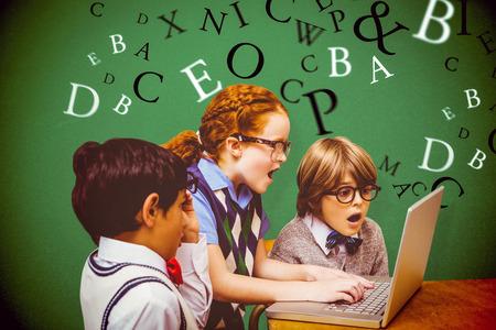 taken: Pupils using laptop against green