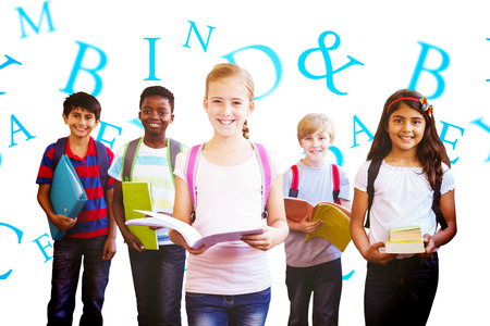 hispanic kids: Smiling little school kids in school corridor against letters Stock Photo