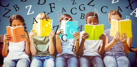 Los niños la lectura de libros en el parque contra el fondo azul Foto de archivo - 43972332