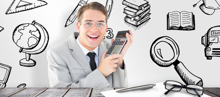 geeky: Geeky smiling businessman holding calculator against desk Stock Photo