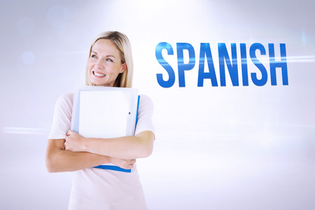 mature student: The word spanish and mature student smiling against grey background Stock Photo