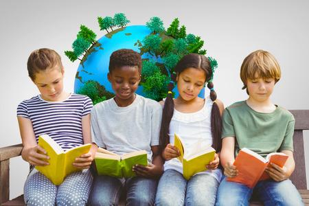 Children reading books at park against grey vignette