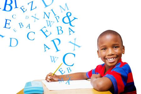 nios en la escuela: Estudiante feliz en el escritorio frente a las letras