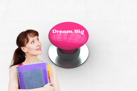 push button: The word dream big and woman holding her school notebooks against pink push button Stock Photo