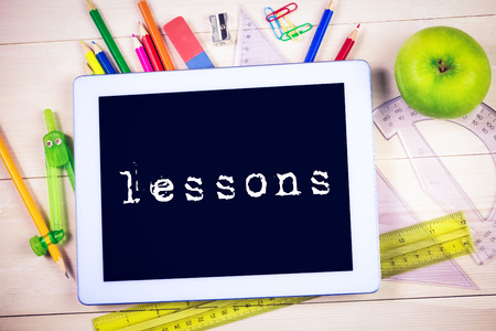 lessons: The word lessons against students table with school supplies