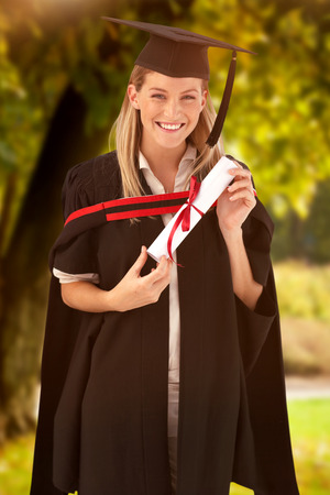 fresh graduate: Woman smiling at her graduation  against trees and meadow in the park Stock Photo