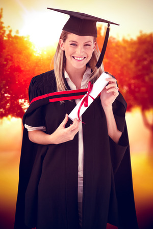 fresh graduate: Woman smiling at her graduation  against sunrise over trees Stock Photo