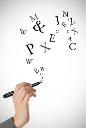 literate: Businesswomans hand writing with marker against letters Stock Photo