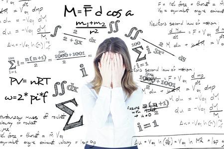 matematicas: Ansioso empresaria con la cabeza en las manos contra ecuación matemática Foto de archivo