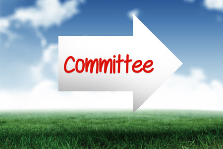 committee: The word committee and arrow against blue sky over green field Stock Photo