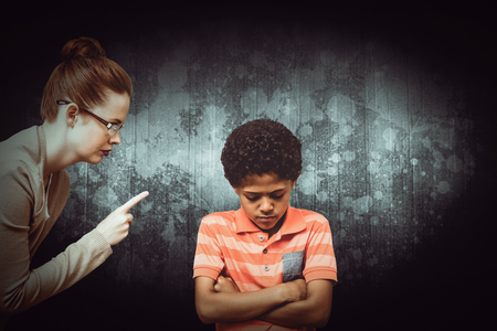 Female teacher shouting at boy against dark background