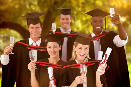 graduacion de universidad: Grupo de personas que gradúa de universidad contra los árboles y pradera en el parque