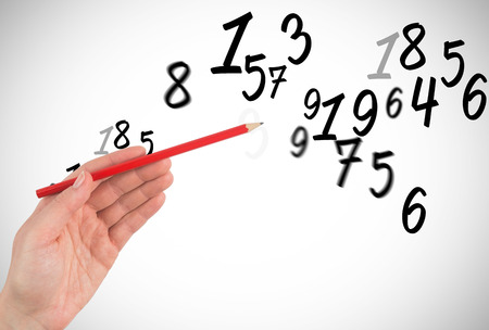 numeracy: Hand holding red pencil  against numbers Stock Photo