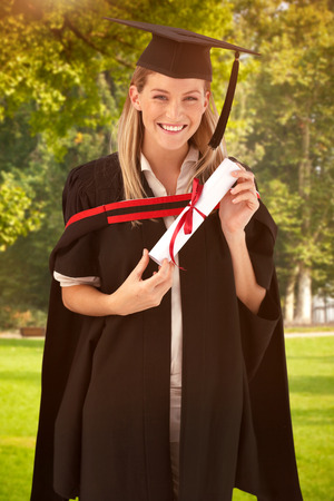 fresh graduate: Woman smiling at her graduation  against trees and meadow