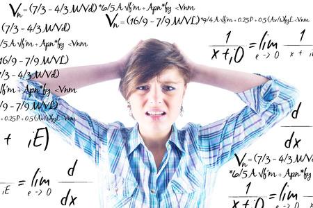 wincing: Pretty brunette getting a headache against maths equation Stock Photo