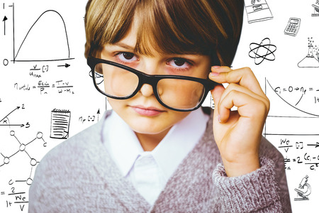 make believe: Cute pupil pretending to be teacher against math and science doodles Stock Photo