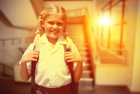 first day of school: Cute pupil smiling at camera by the school bus against empty stair way