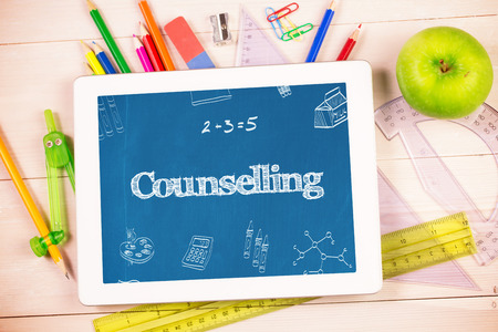 counselling: The word counselling and school doodles against students desk with tablet pc Stock Photo