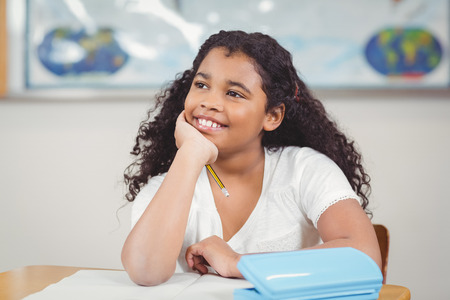daydreaming: Cute pupil daydreaming in a classroom in school Stock Photo