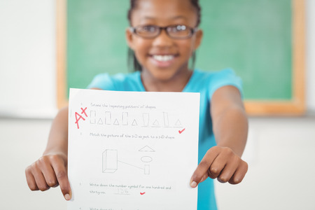 test result: Portrait of proud pupil showing test result to camera in a classroom