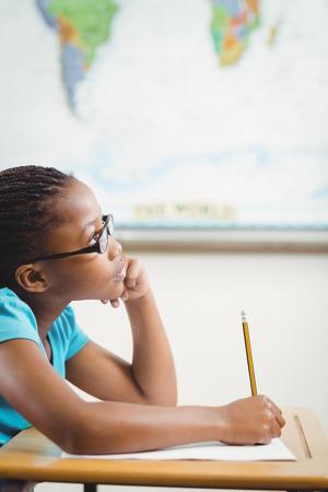 ni�os pensando: alumno centrado trabaja en su escritorio en un aula en la escuela