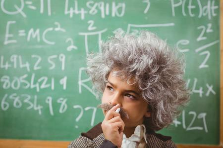 the elderly tutor: Portrait of little Einstein thinking in front of chalkboard in a classroom