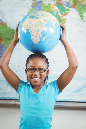 planeta tierra feliz: Portrait of smiling pupil holding globe in front of world map in a classroom