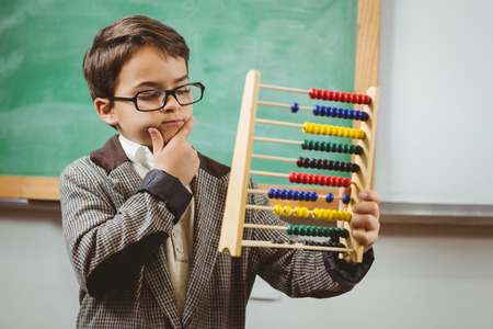 early childhood: Pupil dressed up as teacher holding abacus in a classroom