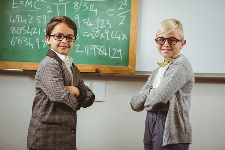 the elderly tutor: Portrait of smiling pupils dressed up as teachers in a classroom in school