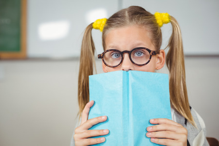covering the face: Portrait of cute pupil covering face with a book in a classroom in school