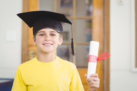 graduacion ni�os: Portrait of smiling pupil with mortar board and diploma in a classroom