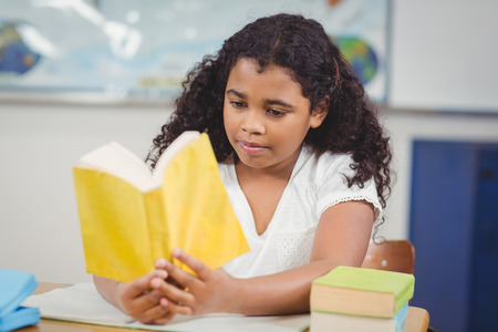 concentrated: Concentrated pupil reading book in a classroom in school Stock Photo