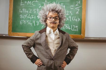 Portrait of little Einstein posing in front of chalkboard in a classroom Stock Photo