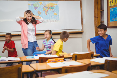 Students driving the teacher crazy at the elementary school Stock Photo