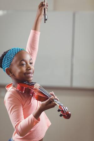 ni�os jugando: estudiante sonriente tocando el viol�n en un aula en la escuela Foto de archivo