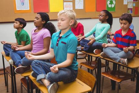 mujer meditando: Los alumnos meditando en los escritorios de aula en la escuela primaria Foto de archivo