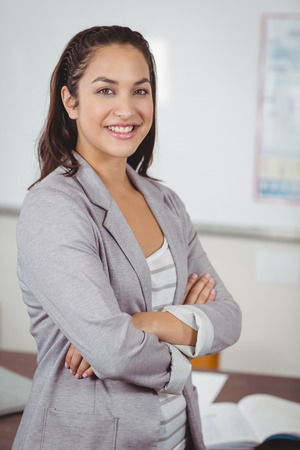 teaching adult: Portrait of pretty teacher with arms crossed in a classroom in school