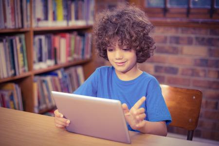 nios en la escuela: Lindo alumno usa la tableta en la biblioteca en la escuela