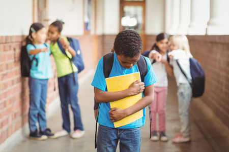 teasing: Sad pupil being bullied by classmates at corridor in school Stock Photo