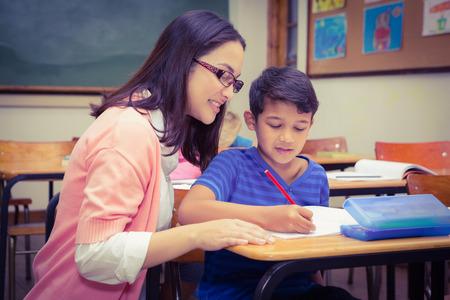 personas ayudando: Profesor feliz ayudando a sus alumnos en la escuela primaria Foto de archivo