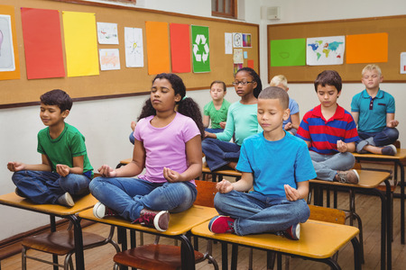 Pupils meditating on classroom desks at the elementary school