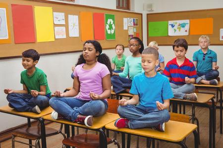 salon de clases: Los alumnos meditando en los escritorios de aula en la escuela primaria Foto de archivo