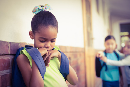 Sad pupil being bullied by classmates at corridor in school Stock Photo