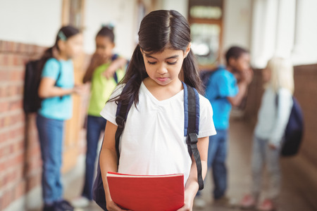 Sad pupil being bullied by classmates at corridor in school Stockfoto