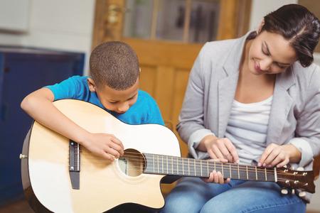 Mooie leraar die gitaarlessen aan leerling in een klaslokaal