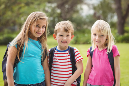 elementary school: Portrait of smiling classmates with schoolbags on campus Stock Photo