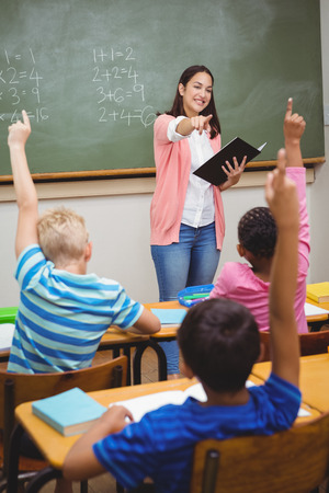 teaching adult: Teacher asking her students a question at the elementary school